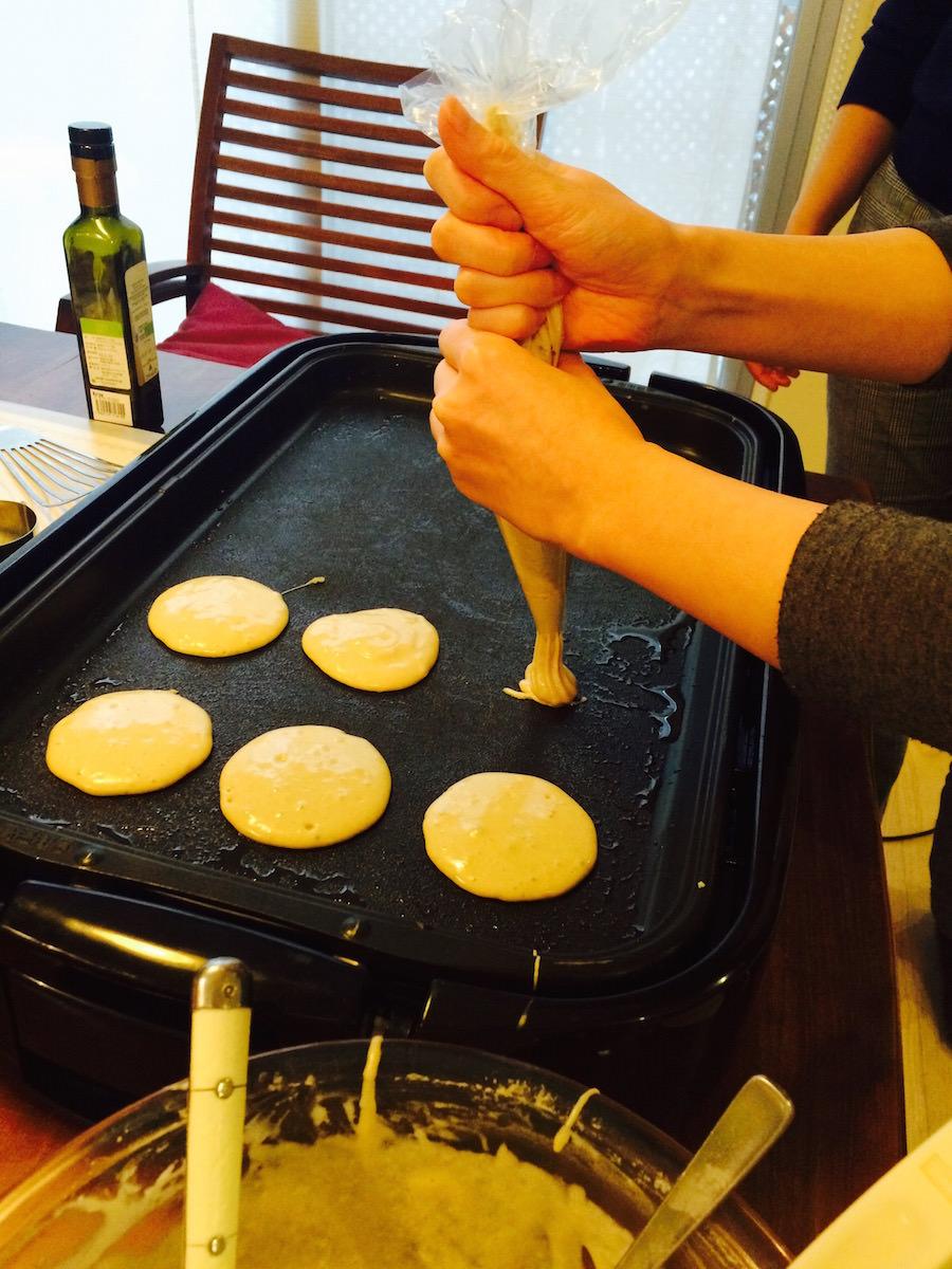 そば粉のパンケーキ「ブリニ」の生地を鉄板に絞リ出す様子