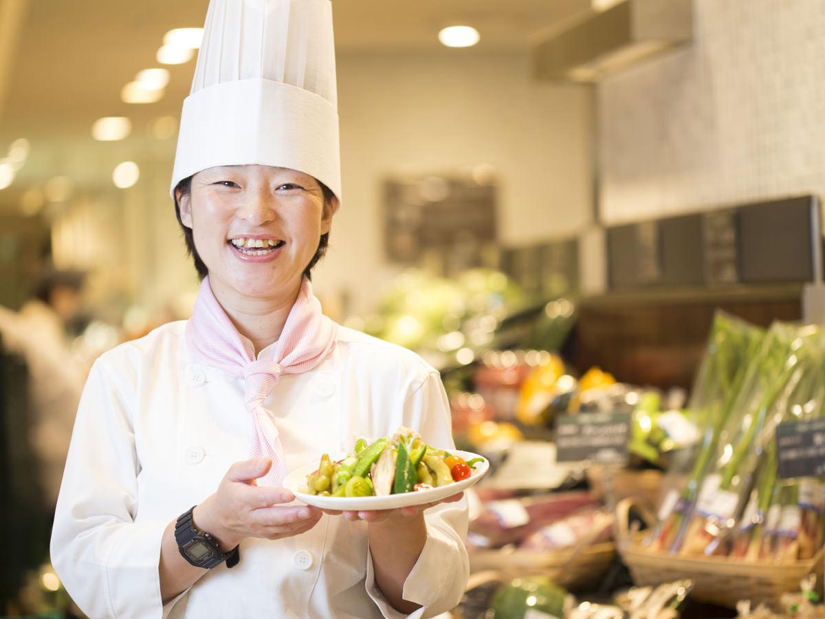 野菜のピクルスを持つ、伊勢丹新宿店フレッシュマーケットの鈴木シェフの画像
