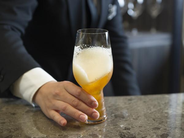 ヒューガルデン・ホワイトの入ったグラスを回して泡立てる