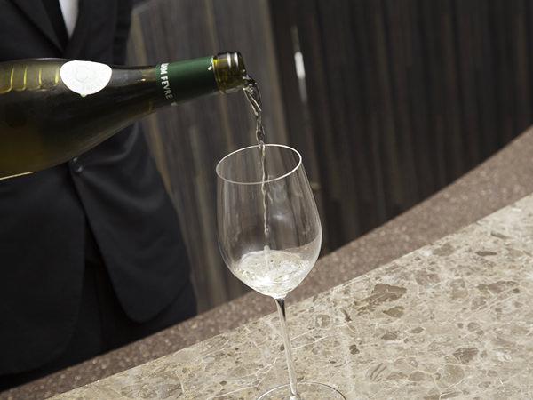 グラスに白ワインを注ぐリーデル店長