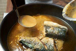 鯖を煮ているところに味噌を加えている様子