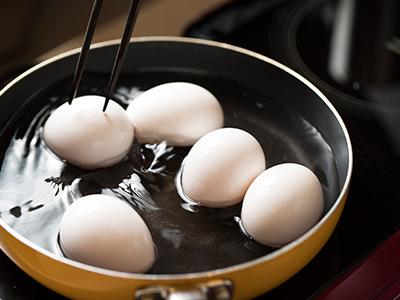 沸騰するまで箸で卵を転がすと黄身が真ん中にくる。沸騰したらふたをする