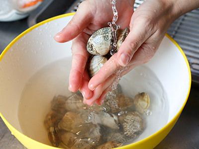 流水でカラをこすり洗いする