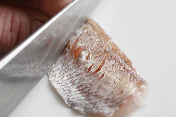 魚の皮目に切り込みを入れる様子