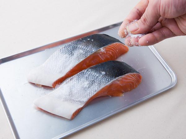鮭に塩を振っている様子