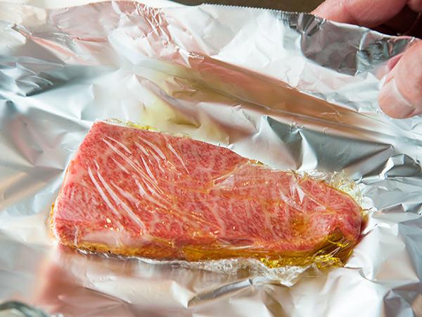 オイルをまぶしてラップで包んだ肉をさらにアルミホイルで包むところ