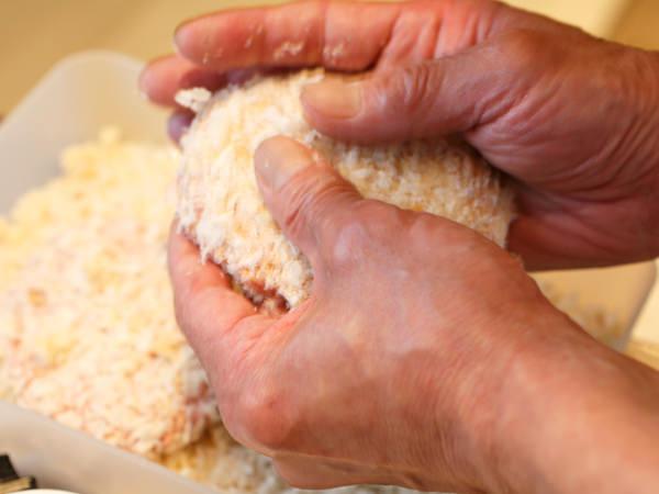 メンチカツの肉ダネにパン粉をつけているところ