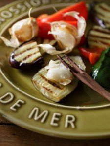 揚げにんにくをつぶして、グリル野菜につけているイメージ