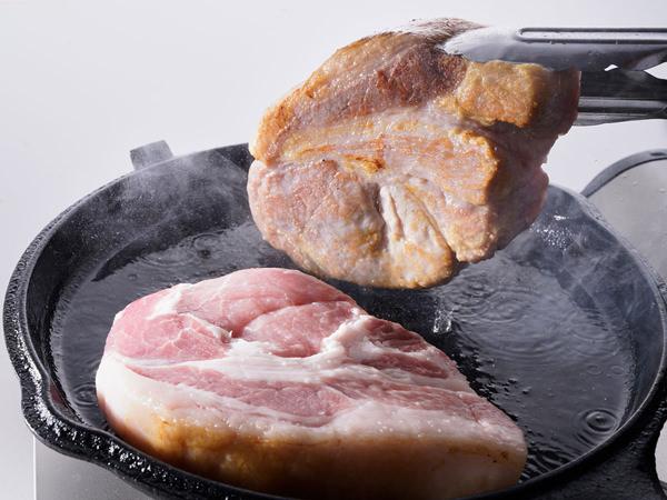 氷温熟成 氷室豚ロース肉の両面をきつね色に焼く様子