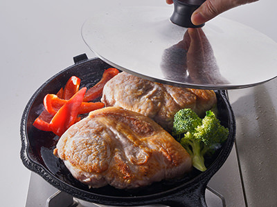 焼いた氷温熟成 氷室豚に野菜を加えて蒸し焼きにする様子