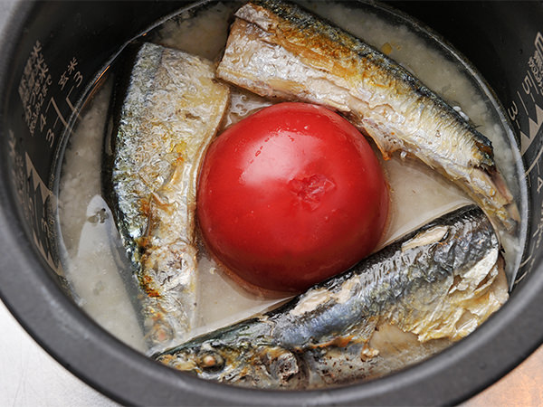 炊飯窯に米、水、調味料、さんま、トマトを入れて炊く