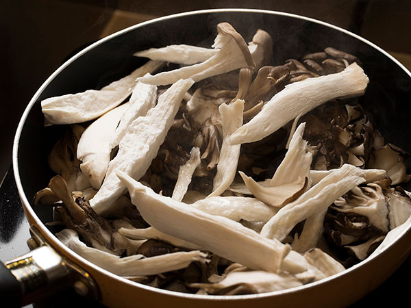 フライパンに舞茸、エリンギを入れて焼く様子