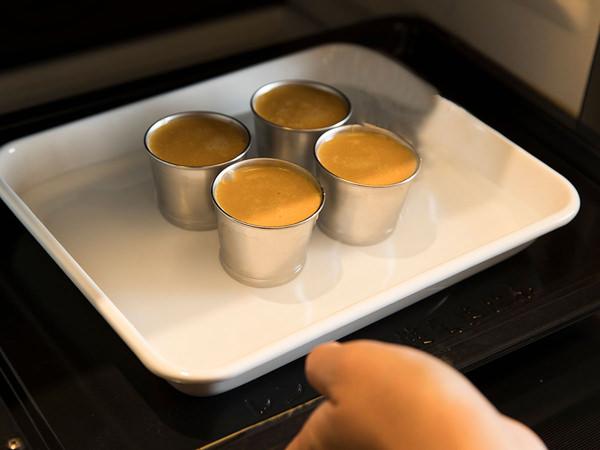プリン液を流し入れたプリンカップを、オーブンで蒸し焼きにする様子