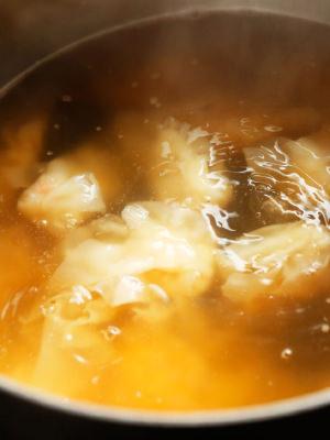 スープの中にワンタンを入れて煮る様子