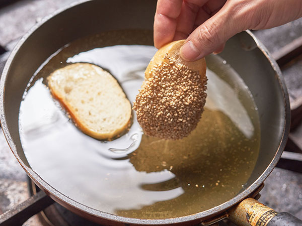 えびトーストを揚げ油に入れる様子