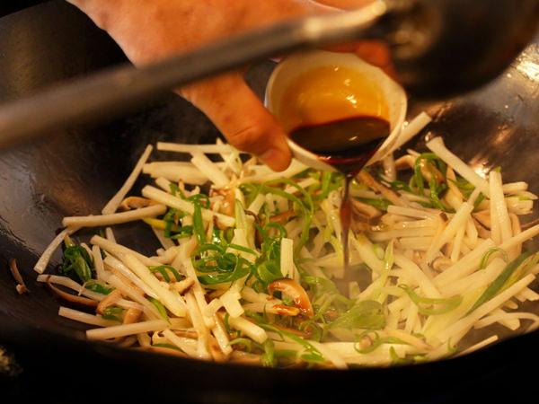 野菜を炒めてしょうゆを加える様子