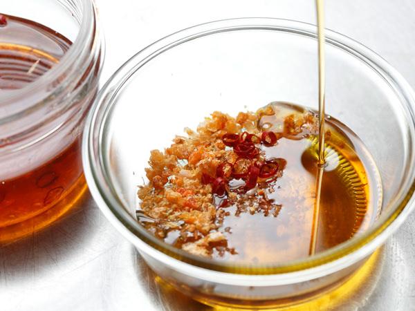 保存容器に干しえび、赤唐辛子を入れ、ごま油を注ぐ様子