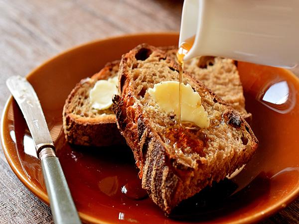 町村農場の発酵バターの食べ方イメージ(ライ麦パンに塗っているところ)