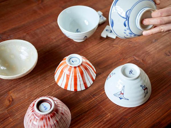 持ち寄った茶碗を並べ、茶碗を手に取っているところ