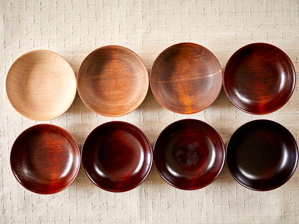 木の器体に漆を塗り重ねた、8段階の漆器の比較