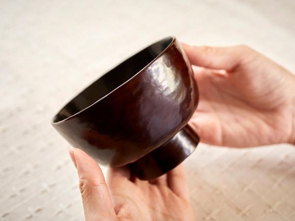漆器の汁椀を手に持っているところ