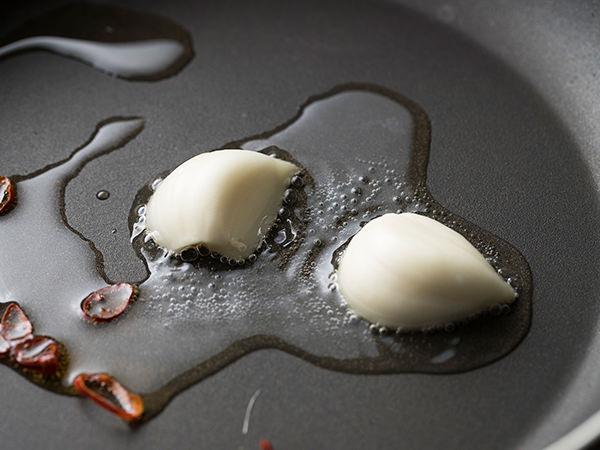 フライパンにオリーブオイル、にんにく、赤唐辛子を入れた写真