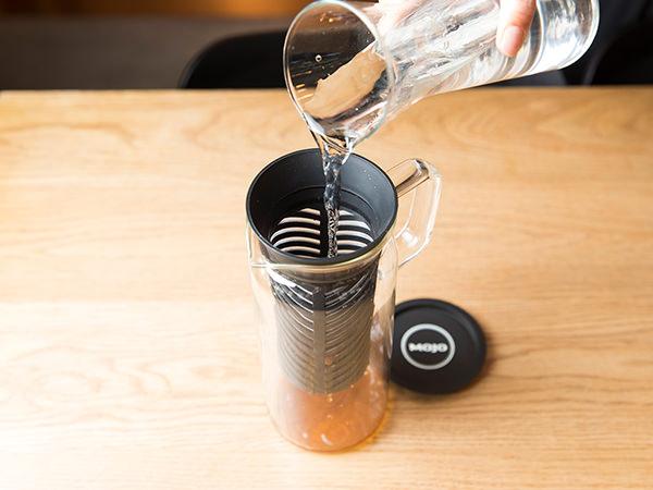 コーヒーを入れたポットに水を注ぐ