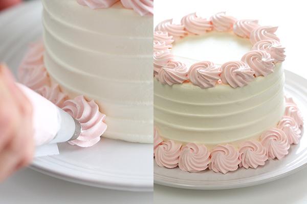 ピンク色の生クリームを絞り終えたケーキ