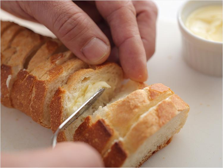 バゲットにバターを塗っている様子