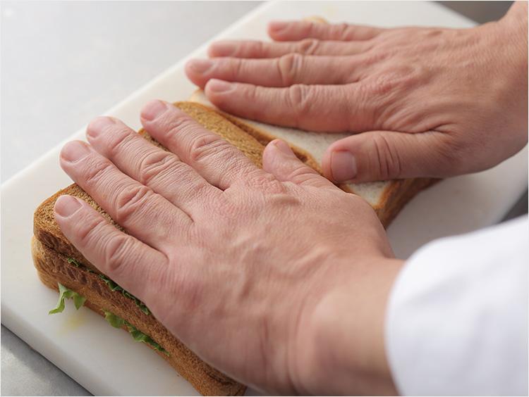 サンドイッチを手で押さえている様子