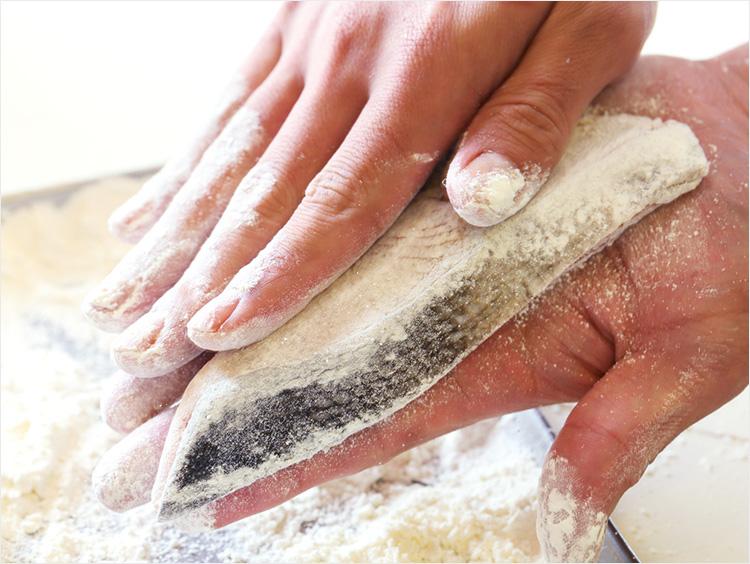 鮭に小麦粉をまぶしている様子