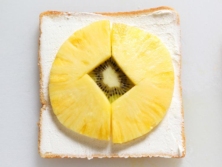 パンにパイナップルを並べている様子